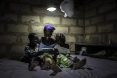 african woman using baobao solar in uncompleted building
