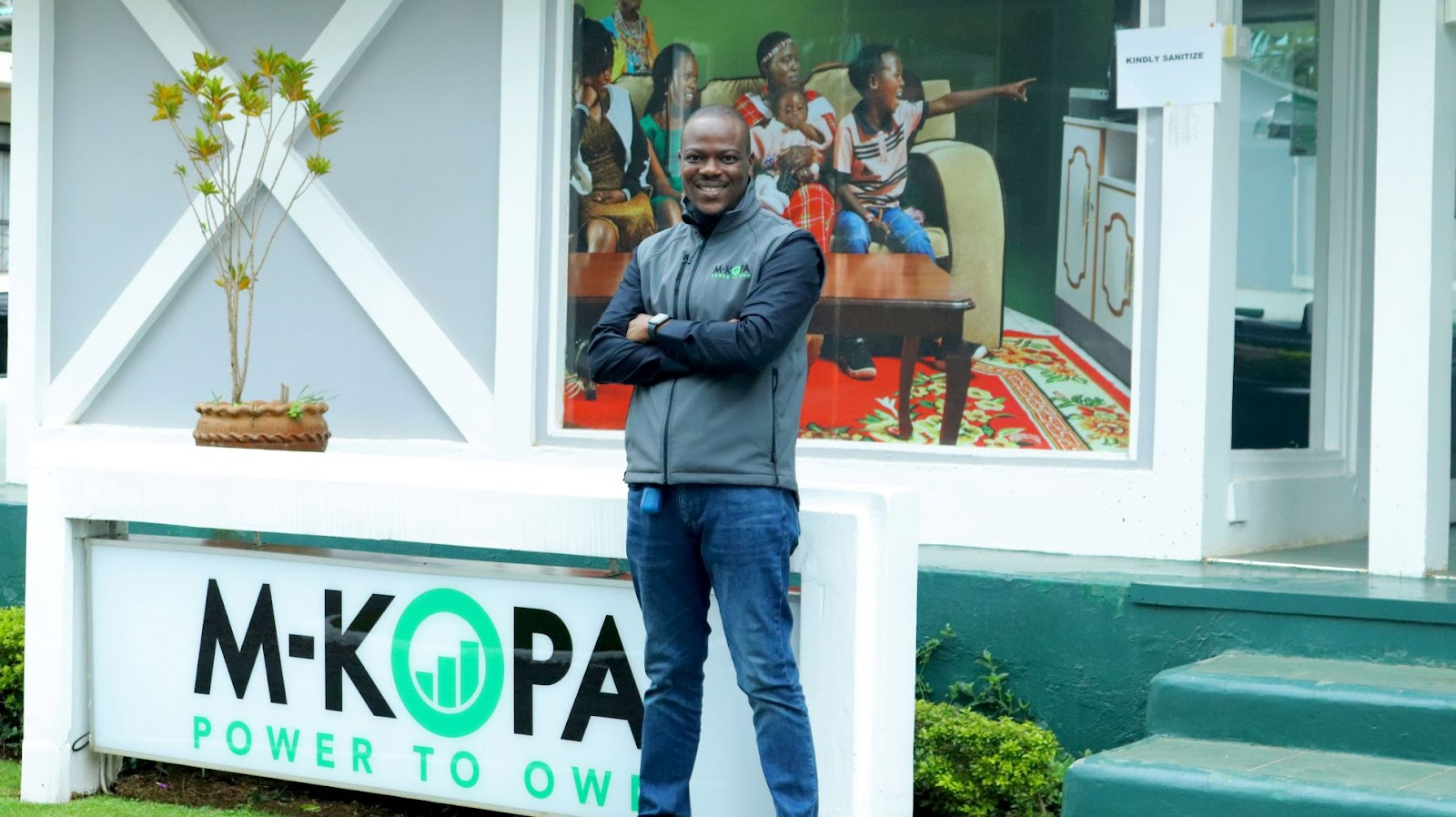 Babajide Duroshola standing in front of M-KOPA's logo